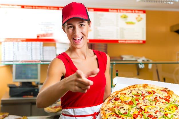 Frau, die in der hand eine ganze pizza hält