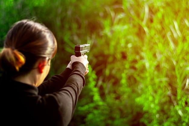 Frau, die in der hand eine gewehr hält. - gewalt- und verbrechenskonzept.