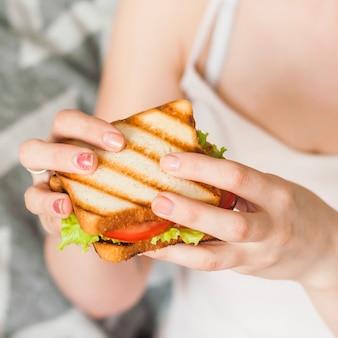 Frau, die in der hand gegrilltes sandwich isst