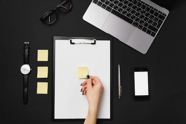 Frau, die in der hand gelbes papier für notizen mit einem fragezeichen hält. draufsicht des schwarzen bürodesktop mit laptop, telefon mit weißem bildschirm und liefert hintergrund.