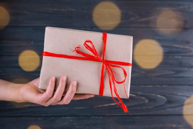 Frau, die in der hand geschenkbox hält