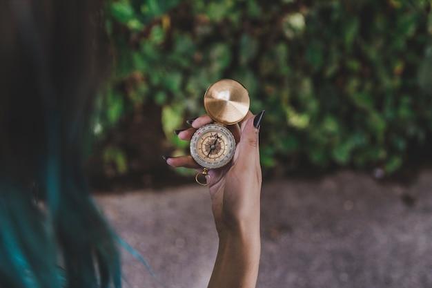 Frau, die in der hand goldenen weinlesekompaß betrachtet