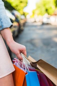 Frau, die in der Hand helle Einkaufstaschen hält