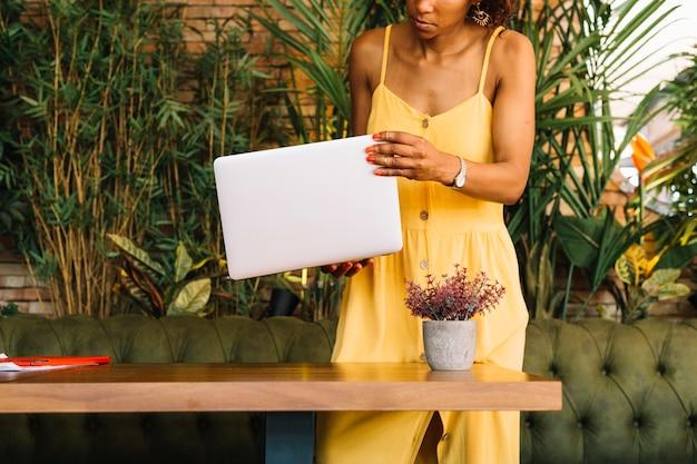 Frau, die in der hand hinter dem holztisch hält laptop steht