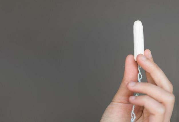 Frau, die in der hand menstruationstampon, menstruationstampon hält. menstruationszeit.