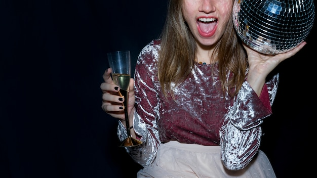 Frau, die in der hand mit glänzender discokugel sitzt