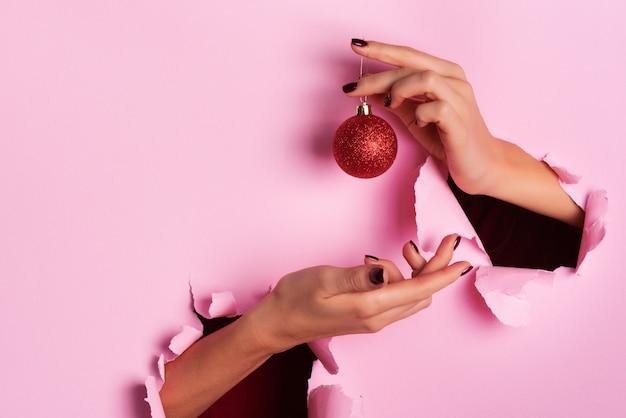 Frau, die in der hand roten funkelnden weihnachtsball über rosa hintergrund mit schnee, helles bokeh hält.