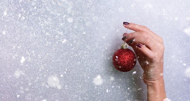 Frau, die in der hand roten funkelnden weihnachtsball über silbernem hintergrund mit schnee, helles bokeh hält.
