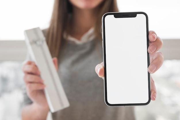 Frau, die in der hand smartphone zeigt