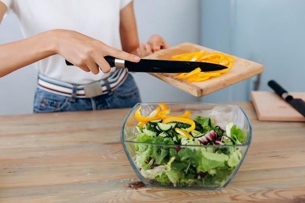 Frau, die in der küche arbeitet, die das gemüse hackt. frau, die pfeffer für salat schneidet. schließen sie herauf chefausschnittgemüse.