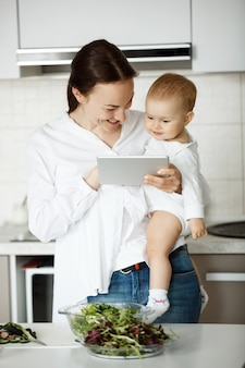 Frau, die in der küche mit baby in den händen steht und etwas auf digitalem tablettbildschirm zeigt