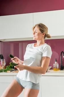 Frau, die in der küche mit gurken tanzt