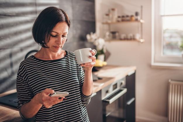 Frau, die in der küche steht und intelligentes telefon verwendet