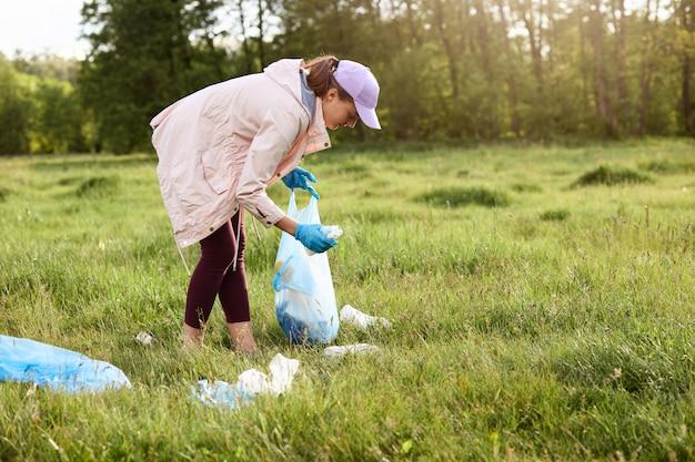 Frau, die in der mitte des feldes zwischen verstreutem stoff und müllsack hält und müll während des sonnenuntergangs pflückt. umweltverschmutzungskonzept, müll sammeln.