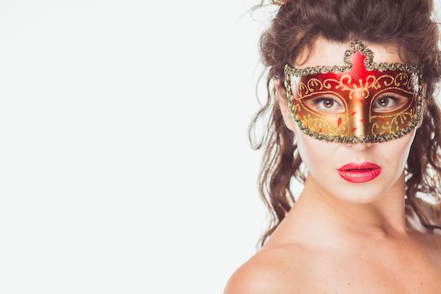 Frau, die in der roten und goldenen maske aufwirft