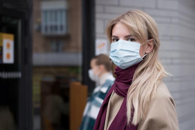 Frau, die in der schlange auf der straße außerhalb der tür während der coronavirus-pandemie wartet Premium Fotos