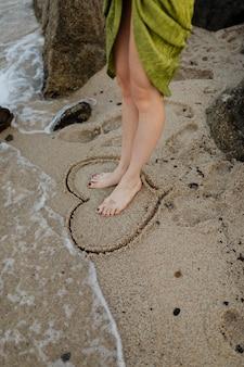 Frau, die in der seite ein zeichnendes herz am strand steht