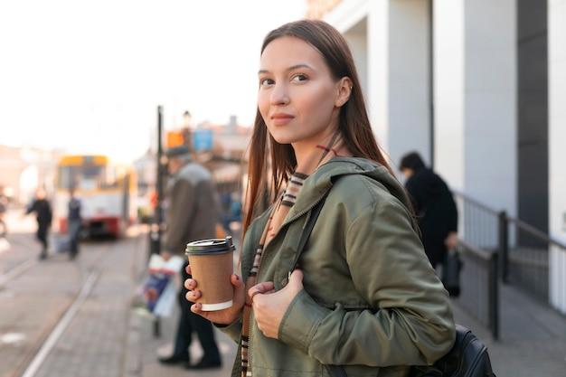 Frau, die in der seitenansicht der straßenbahnstation wartet
