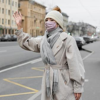 Frau, die in der stadt beim tragen der medizinischen maske winkt