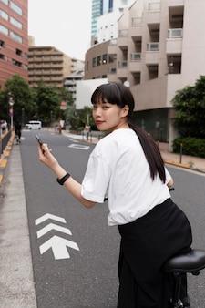 Frau, die in der stadt elektrofahrrad fährt und smartphone hält