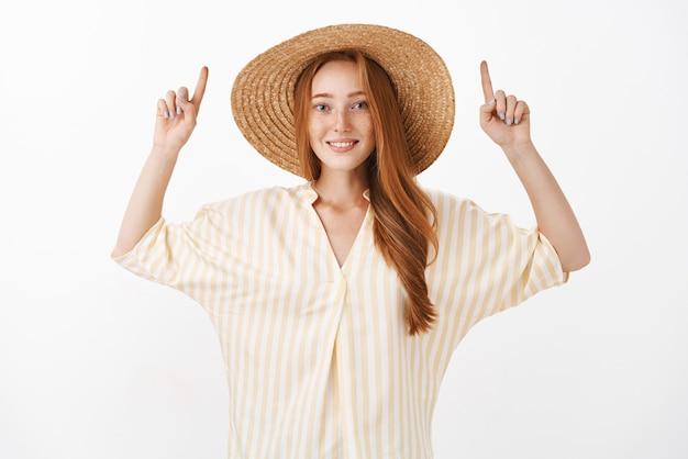 Frau, die in der trendigen gelben bluse und im sommerstrohhut steht, die arme anheben und freudig über graue wand lächeln