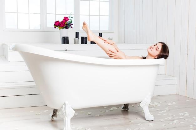 Frau, die in der wanne im eleganten badezimmer sich entspannt