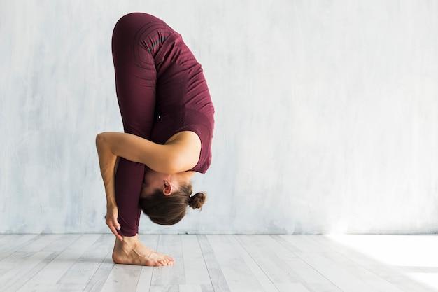 Frau, die in der yogahaltung des großen zehs steht