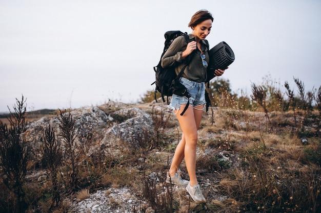 Frau, die in die berge mit reisetasche geht