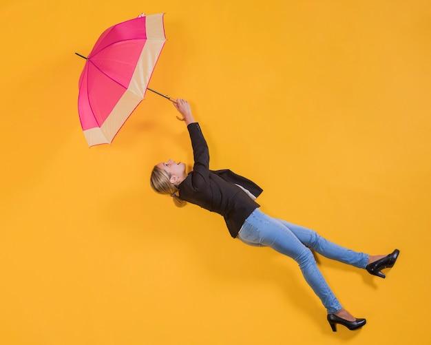 Frau, die in die luft mit einem regenschirm schwimmt