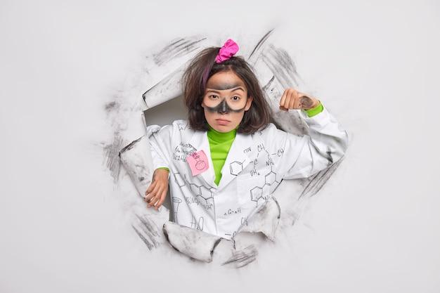 Frau, die in eigener macht versichert ist, hebt arm zeigt muskeln beendet arbeit am experiment, gekleidet in medizinischem kittel, bricht durch papier