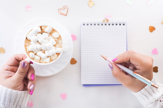 Frau, die in ein notizbuch schreibt und tasse heißen kakao mit marshmallows hält