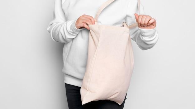 Frau, die in eine einkaufstasche schaut