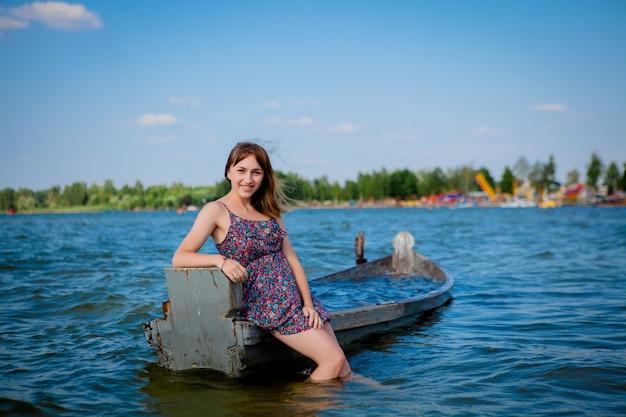 Frau, die in einem alten hölzernen boot auf einem großen see sitzt