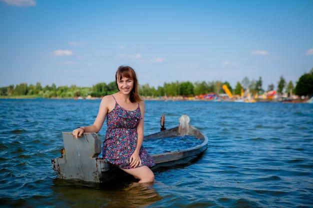 Frau, die in einem alten hölzernen boot auf einem großen see svityaz sitzt. konzept des sommers