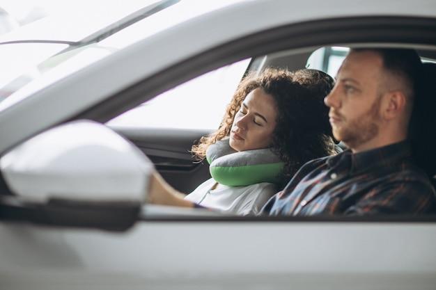 Frau, die in einem auto auf einem autokissen schläft