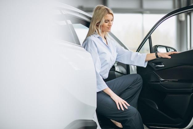Frau, die in einem auto in einem autosalon sitzt