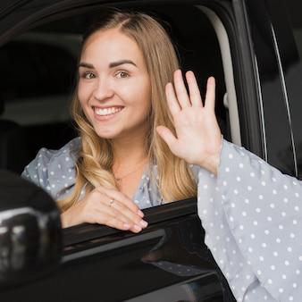 Frau, die in einem auto und in einer begrüßung stationiert