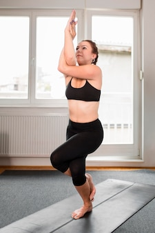 Frau, die in einem bein yoga zu hause konzept steht