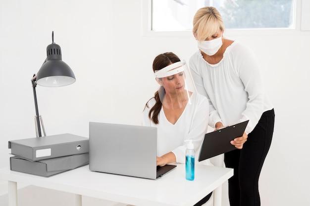 Frau, die in einem büro arbeitet und gesichtsschutz-vorderansicht trägt