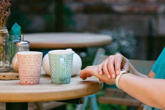 Frau, die in einem café sitzt und auf jemanden wartet, der auf ihre uhren schaut