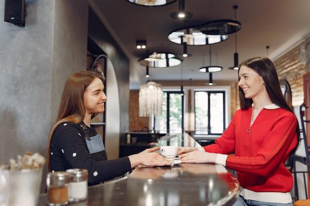Frau, die in einem café sitzt und mit barista spricht