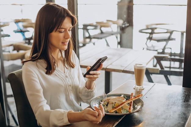 Frau, die in einem café zu mittag isst und salat isst