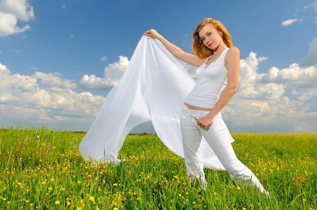 Frau, die in einem grünen feld mit luftiger seide aufwirft