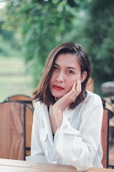 Frau, die in einem holzstuhl in einem restaurant sitzt