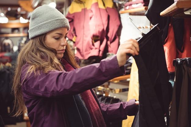 Frau, die in einem kleidergeschäft einkauft