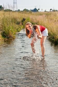 Frau, die in einem kleinen nebenfluss mit ihren knöcheln im wasser steht