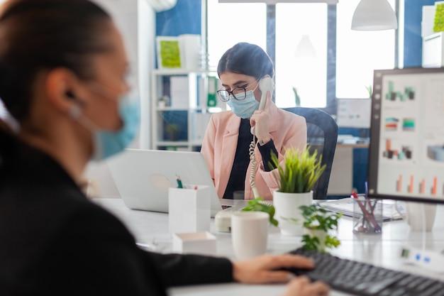Frau, die in einem neuen normalen büro am telefon diskutiert und eine gesichtsmaske als sicherheitsvorbeugung hinter einem plastikschild trägt und während des ausbruchs der coronavirus-grippe soziale distanz zu ihrem kollegen hält.