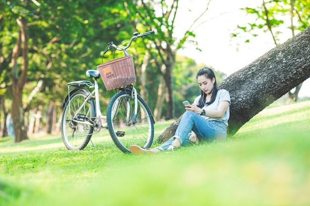 Frau, die in einem park sich lehnt auf einem baum sitzt und musik auf kopfhörern mit einem fahrrad hört