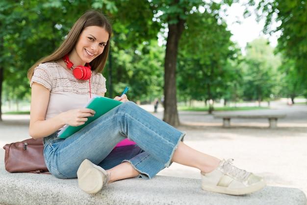 Frau, die in einem park vor der schule studiert