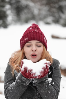 Frau, die in einem schneehaufen bläst